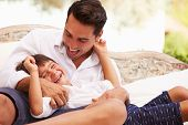 foto of tickle  - Father At Home Sitting On Outdoor Seat And Playing With Son - JPG