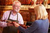 Customer Leaving Violin For Repair In Shop