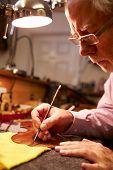 Man Restoring Violin In Workshop