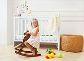 pic of paint horse  - Little cute girl in nursery room with basket toys and wooden horse - JPG