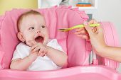 stock photo of feeding  - Happy Baby Girl Getting Feeded in the high chair - JPG