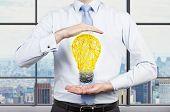 Businessman Holding Yellow Bulb