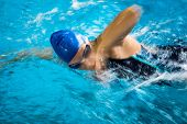 Female swimmer in an indoor swimming pool - doing crawl (shallow DOF; motion blur technique used to convey fast movement of the swimmer)