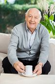 Portrait of happy senior man having coffee on couch at nursing home porch