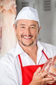Closeup portrait of confident male butcher holding meat in butchery