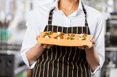 Midsection of female chef holding stuffed ravioli pasta sheet in commercial kitchen
