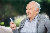 Senior man looking at cards while sitting on couch at nursing home porch