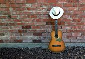 picture of panama hat  - Guitar player takes a break leaving old acoustic guitar Blues Harp and Panama Hat leaning against a brick wall - JPG