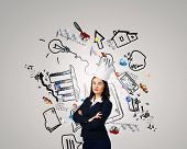 Young businesswoman in paper crown and sketches at background
