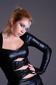 Pretty young woman in skintight cyber style clothing and make-up, against the grey background