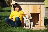 Boy with his new puppy sitting in front of the doghouse