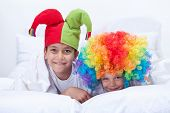 Happy kids with clown hat and hair playing indoors