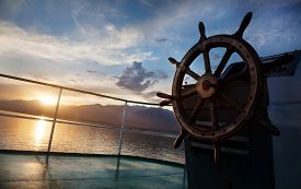 picture of sailing vessels  - Wooden wheel on the ship at sunset on Issyk Kul lake - JPG