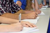 stock photo of students classroom  - Side view mid section of students writing notes in classroom - JPG