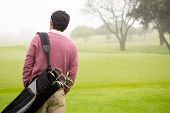 picture of golf bag  - Golfer walking and holding his golf bags in golf course - JPG