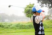 foto of take off clothes  - Golfer teeing off at the golf course - JPG