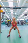 picture of kettlebell  - Portrait of beautiful woman lifting black iron kettlebell in a crossfit training on fitness center - JPG