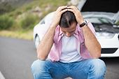 stock photo of breakdown  - Stressed man after a car breakdown at the side of the road - JPG