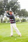 picture of swings  - Golfer swinging his club on the course on a foggy day at the golf course - JPG