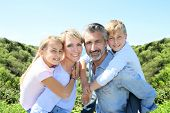 picture of piggyback ride  - Parents giving piggyback ride to kids  - JPG