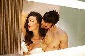image of lovers  - Sexy milf woman with young macho lover posing in mirror - JPG