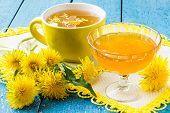 stock photo of dandelion  - Dandelions flower tea and jam of dandelions on a blue wooden background - JPG