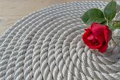 stock photo of arum lily  - Beautiful red rose lily over rope and wooden table - JPG