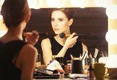 foto of mirror  - Portrait of a beautiful woman as applying makeup near a mirror - JPG