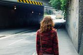 picture of underpass  - A young woman is walking on the street near an underpass - JPG
