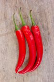 stock photo of chillies  - Hot red chili or chilli peppers over wooden background - JPG