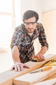 foto of carpenter  - Concentrated young male carpenter sanding wood in his workshop