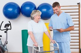 picture of zimmer frame  - Senior woman walking with zimmer frame with therapist in fitness studio - JPG