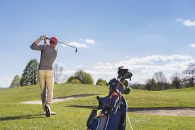 stock photo of swing  - Male golf player swinging golf club - JPG