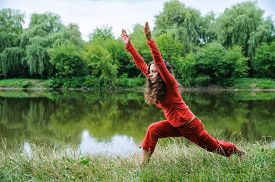 pic of virabhadrasana  - Beautiful young woman performing yoga exercises on the lake - JPG