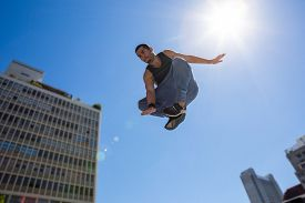 pic of parkour  - Man doing parkour in the city on a sunny day - JPG