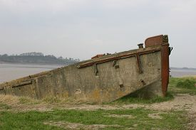 stock photo of barge  - Decaying concrete barge as hulk on river bank - JPG