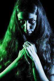 foto of wraith  - Scary face of a young woman in green and grey lights over black background - JPG